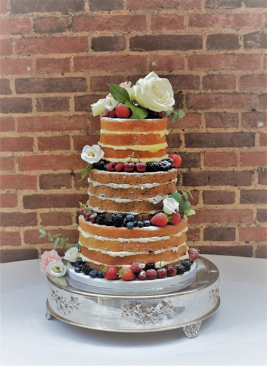 Naked Wedding Cake Decorated With Summer Fruits and Fresh Flowers