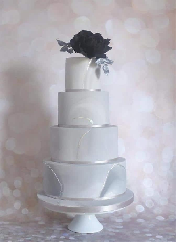 Grey marble cake with edible silver leaf accents topped with a gorgeous large black sugar Rose and silver leaves