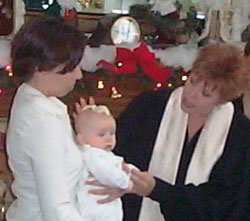 Rev. Deb sprinkling water on the baby's head during a baptism