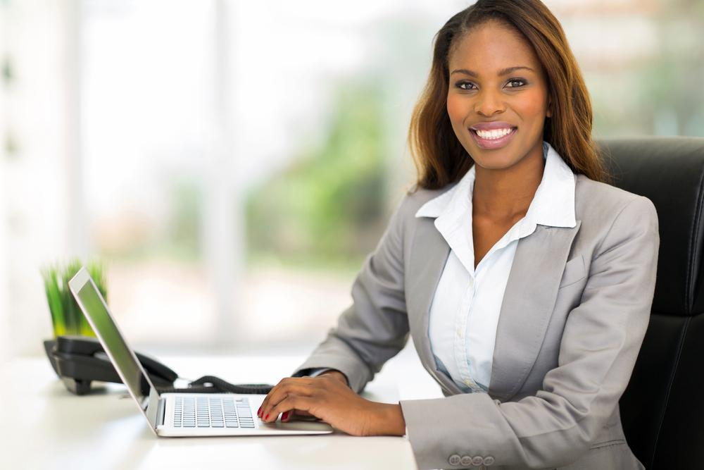Female real estate agent smiling working at her desk on laptop computer